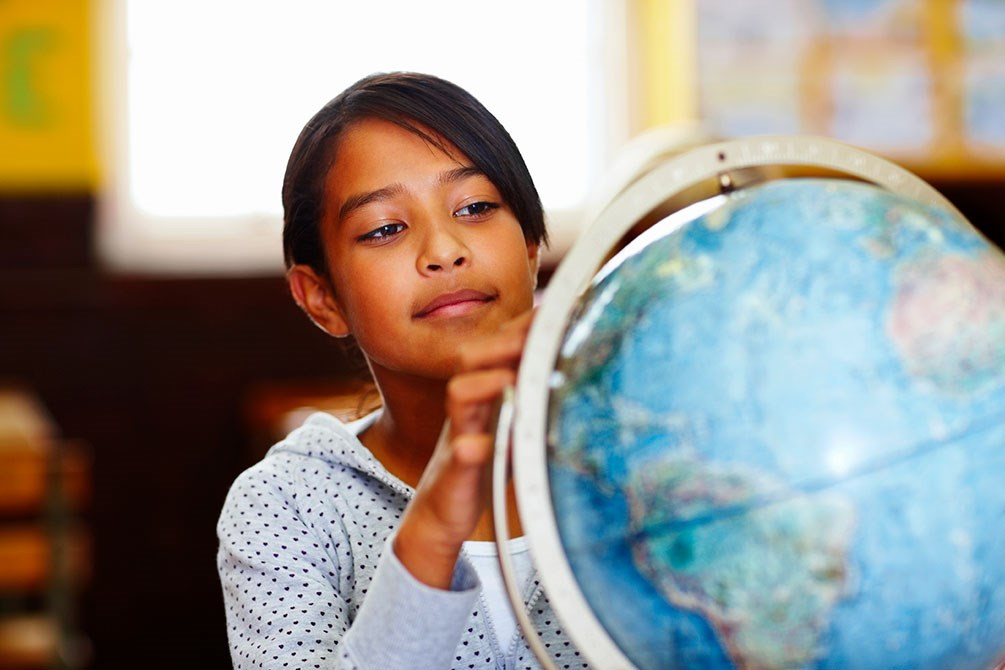 A young student peers at a classroom globe.