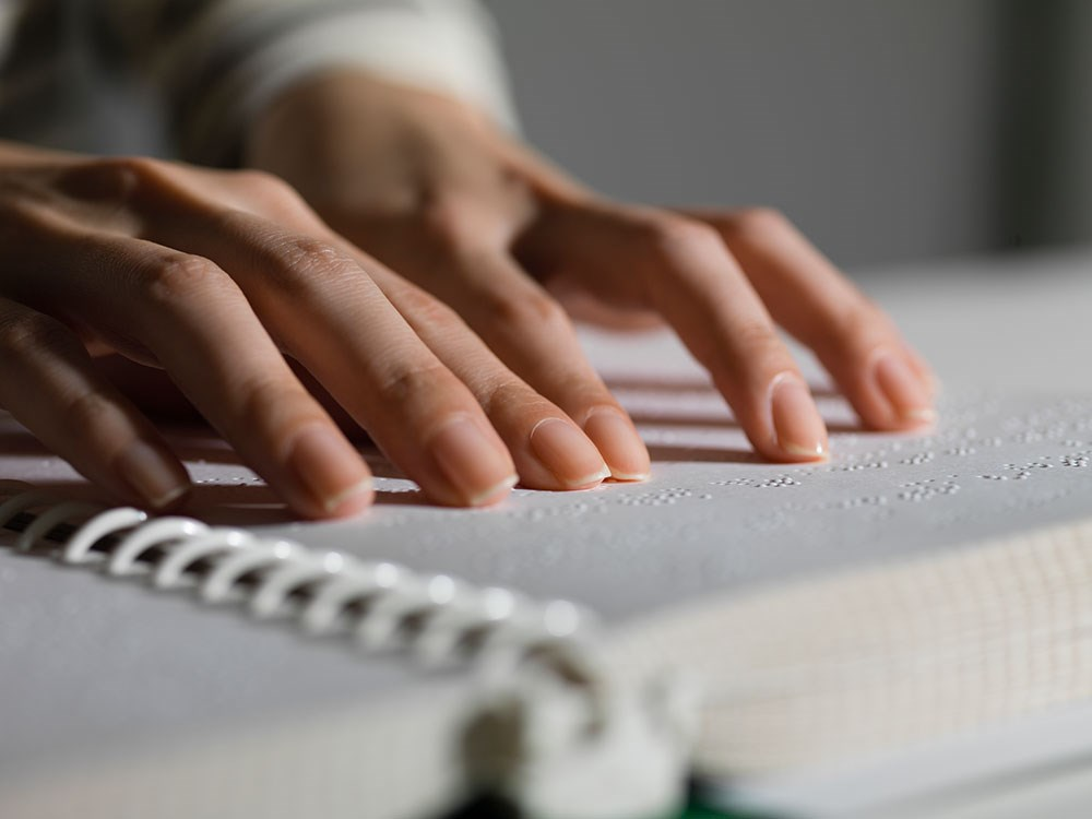 Image of hands reading braille book